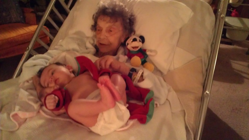 My mom holding Emme, her first great grandchild, with Mickey on her shoulder.